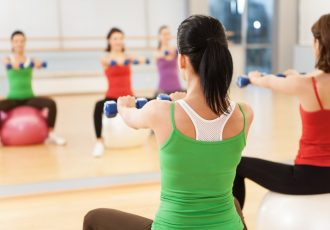 Pilates aerobics women group with stability ball. young girls sitting and holding dumbbells