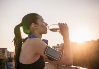 Young woman wearing armband drinking water