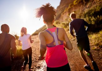 Back view of a group of friends jogging outdoors on a summer afternoon with sun flare