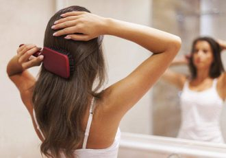 Young-woman-brushing-healthy-hair-in-front-of-a-mirror