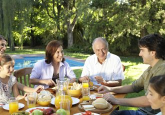 Family, including children (7-11) sitting at table in garden, smiling